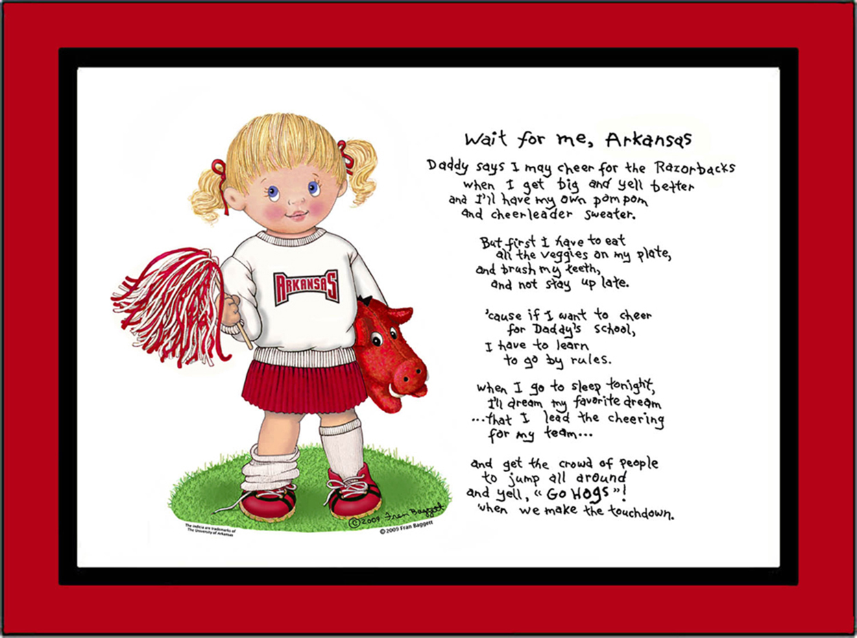 Arkansas toddler cheerleader standing in the grass with her bulldog puppy beside her. She is wearing red bows in her hair, a Arkansas sweatshirt, pleated skirt and sneakers with socks. She is holding a pom pom in one hand.