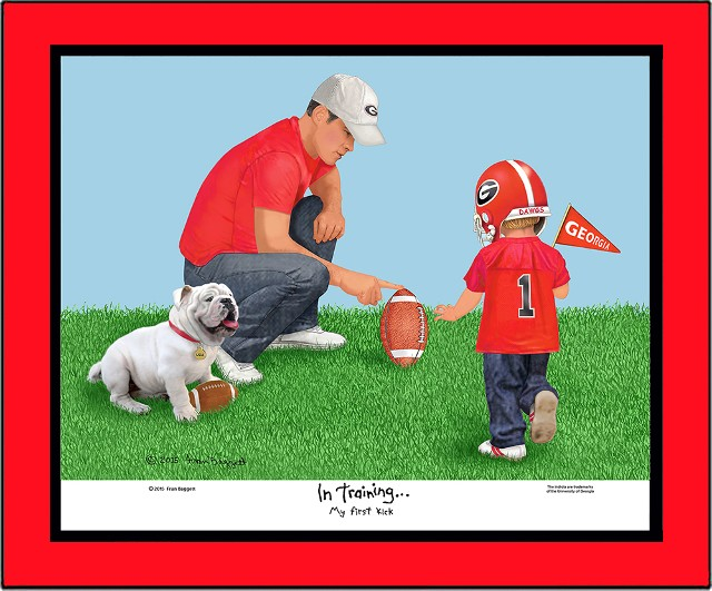 Georgia dad and son with baby bulldog in grass. Dad is holding a football steady for his son to make his first kick. The little boy is wearing a helmet and holding a Georgia pennant in one hand and moving forward to kick the ball. In Training and My First Kick is printed below the graphic.